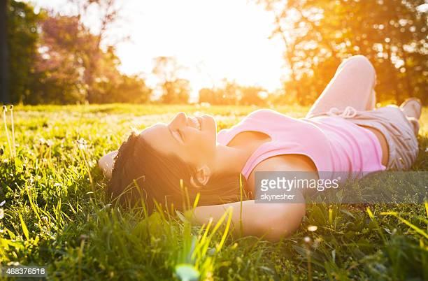 Lächelnd Mädchen in der Wiese liegen und genießen Sie den Sonnenuntergang.