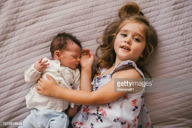 smiling girl lying on blanket cuddling with her baby brother - schwester stock-fotos und bilder
