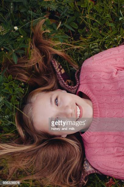 Smiling girl lying on grass with her hair spread out