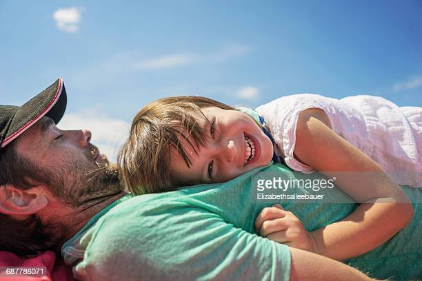 Smiling girl lying on her father's chest