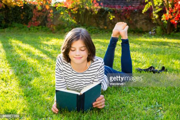 Smiling girl lying on meadow reading a book