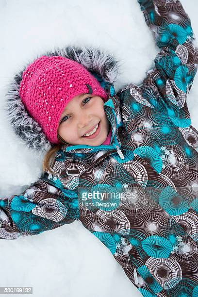 Smiling girl lying on snow