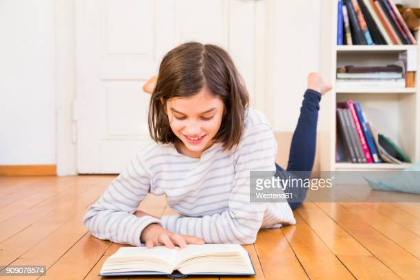 smiling girl lying on the floor reading book - floorboard stock photos and pictures