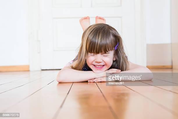 smiling girl lying on wooden floor closing her eyes - 顎に手をやる ストックフォトと画像