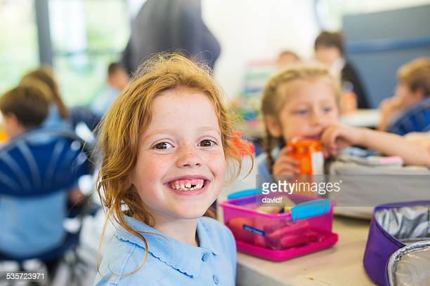 smiling girl missing a tooth with a healthy lunch - schoolkinderen stockfoto's en -beelden