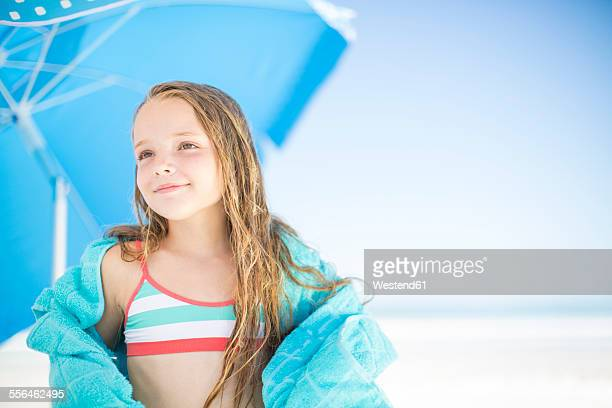 Smiling girl on beach drying off with a beach towel