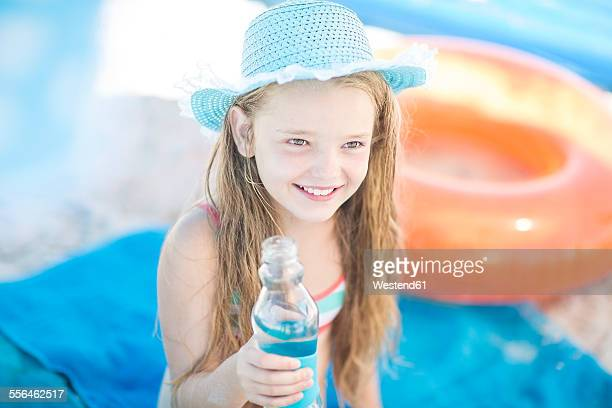 Smiling girl on beach holding a bottle of water