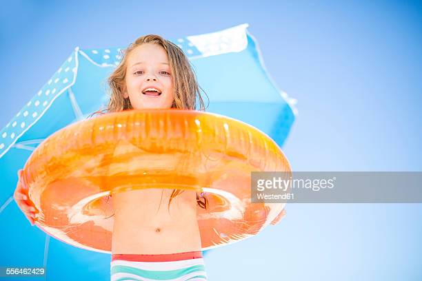 Smiling girl on beach holding an orange floating tyre