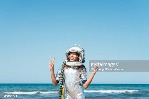a smiling girl on the beach in an astronaut suit with the victory sign in her hands - space helmet stock pictures, royalty-free photos & images