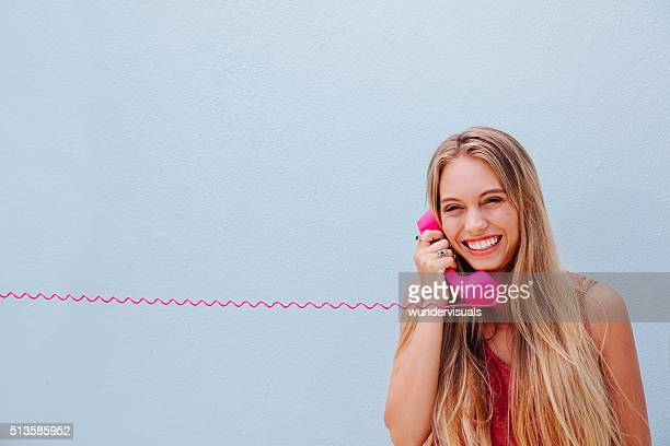 Smiling girl on vintage telephone