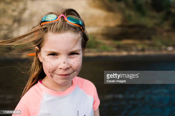 smiling girl on waters edge wearing rashie and googles - google stock pictures, royalty-free photos & images