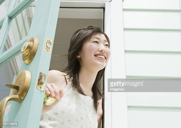 Smiling girl opening the door