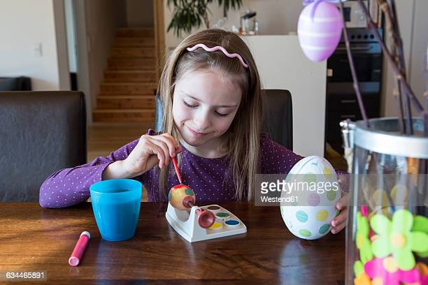 Smiling girl painting Easter egg at home