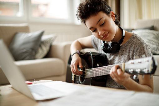 Smiling girl playing a guitar at home 1049430556