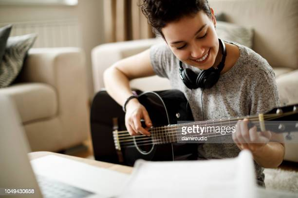 smiling girl playing a guitar at home - guitar stock pictures, royalty-free photos & images