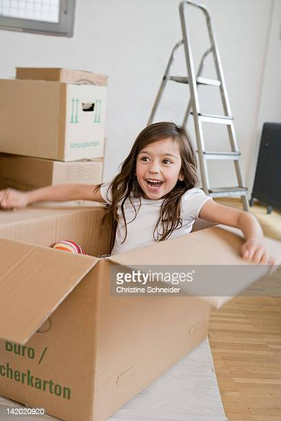 Smiling girl playing in cardboard box