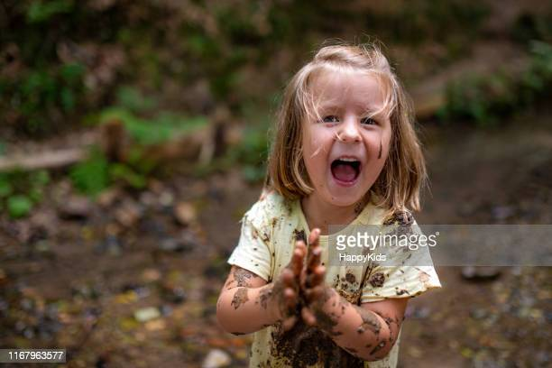 smiling girl playing in forest - primary age child stock pictures, royalty-free photos & images