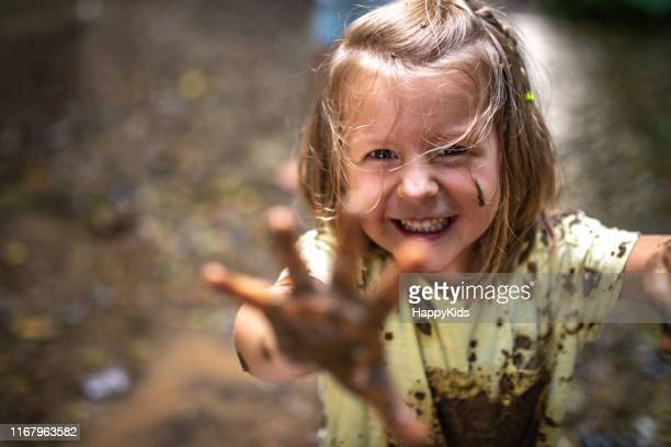 smiling girl playing in forest - mud stock pictures, royalty-free photos & images