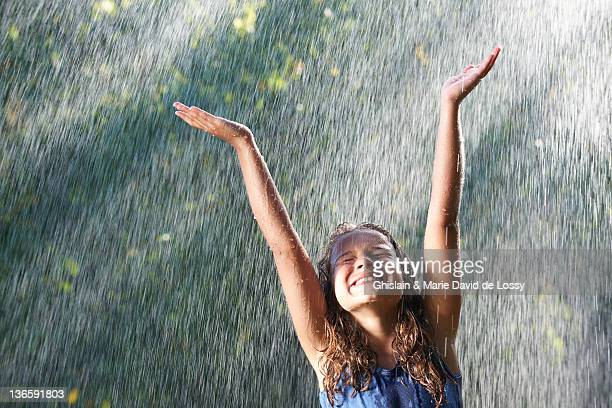 smiling girl playing in rain - rain stock pictures, royalty-free photos & images