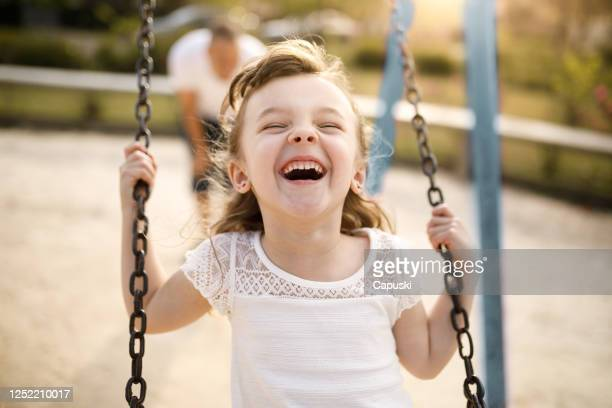 smiling girl playing on the swing - image foto e immagini stock