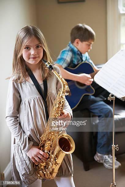 Smiling girl playing saxophone
