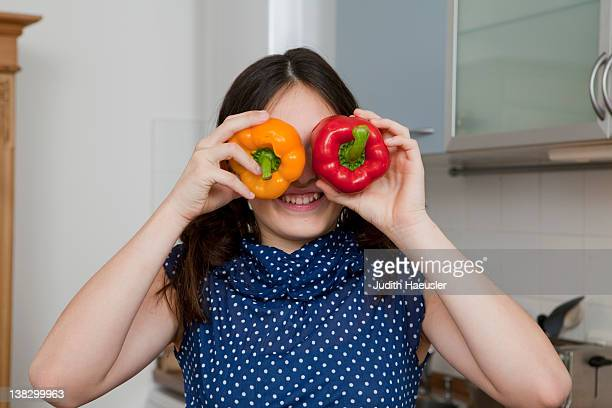 Smiling girl playing with bell peppers
