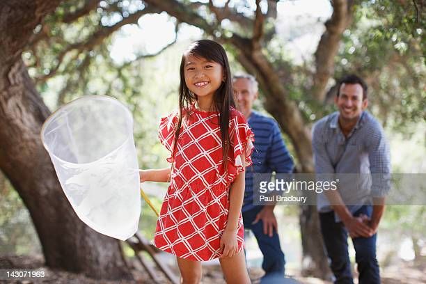 Smiling girl playing with butterfly net
