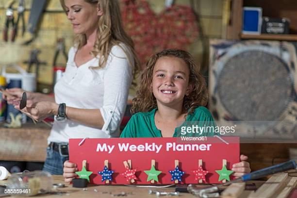 Smiling girl presenting craftwork in home garage
