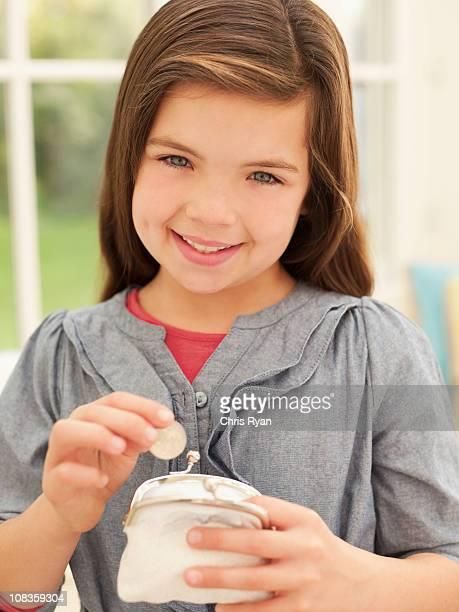 Lächelnd Mädchen putting Geld in Geldbörse