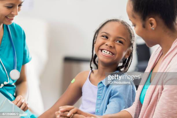 smiling girl receives immunization from nurse - vaccination stock pictures, royalty-free photos & images
