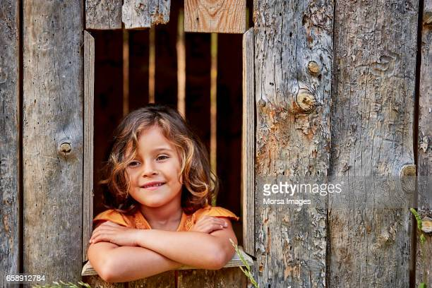 Smiling girl resting on window of log cabin