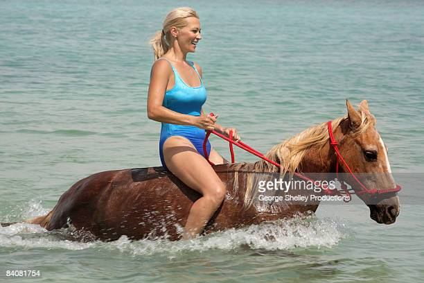 smiling girl riding a horse in the water - waist deep in water stock pictures, royalty-free photos & images