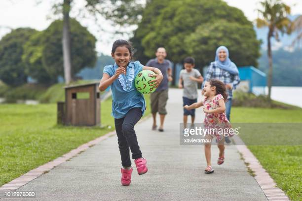 smiling girl running with ball against family - malay stock photos and pictures