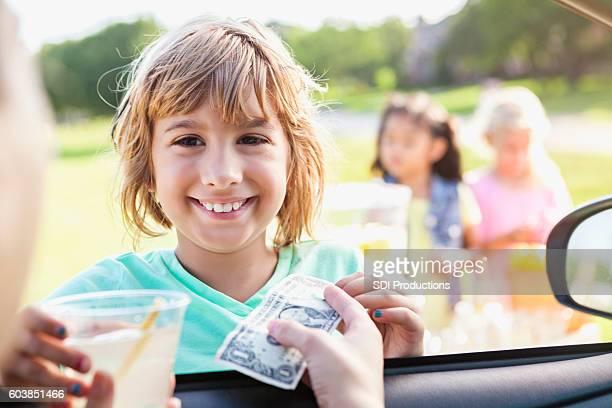 Smiling girl sells lemonade to customer