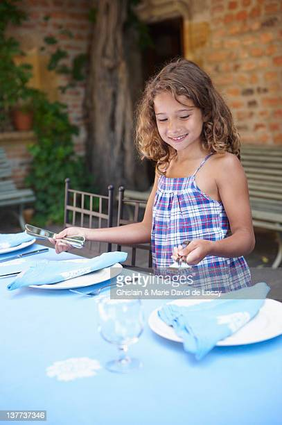 Smiling girl setting table outdoors