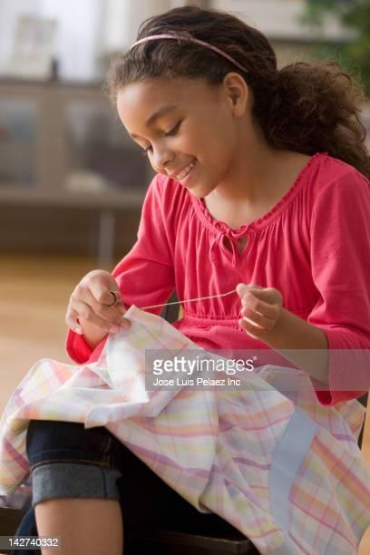 Smiling girl sewing