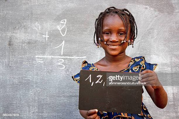 A smiling girl showing a slate