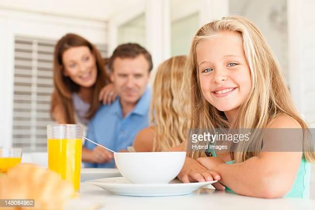 Niña sonriente sentado en la mesa de desayuno