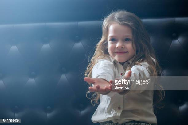 Smiling girl sitting on couch reaching her hands out