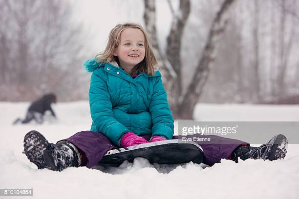 smiling girl sitting on snow bodyboard - ski pants stock pictures, royalty-free photos & images