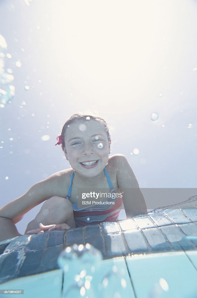 Smiling Girl Sitting on the Edge of a Swimming Pool : Stock Photo