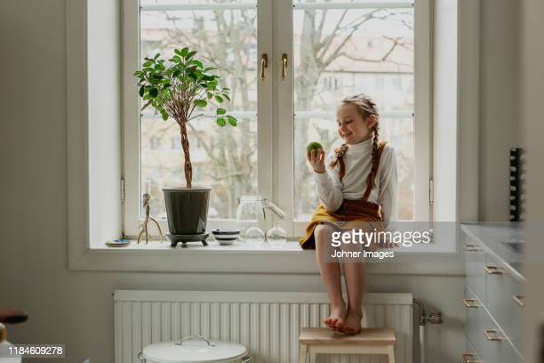 smiling girl sitting on windowsill - solo una bambina femmina foto e immagini stock
