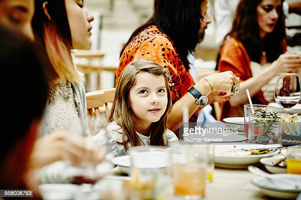 Smiling girl sitting with family during dinner