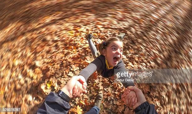 smiling girl spinning and holding dad's hands - drehen stock-fotos und bilder