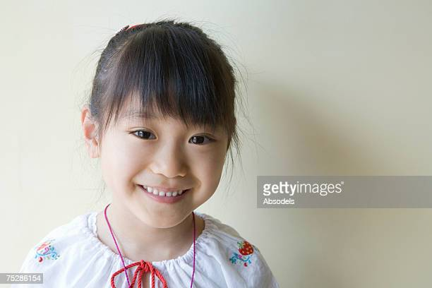 A smiling girl standing against wall