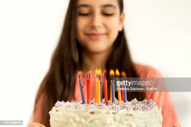 smiling girl standing by birthday cake against wall - birthday candle stock pictures, royalty-free photos & images