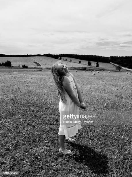 smiling girl standing on field against sky - sibley stock photos and pictures