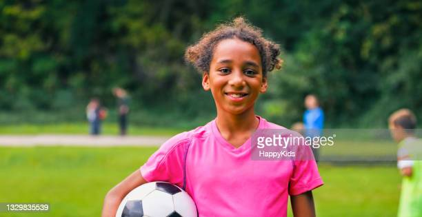 smiling girl standing with football on soccer field - football league stock pictures, royalty-free photos & images