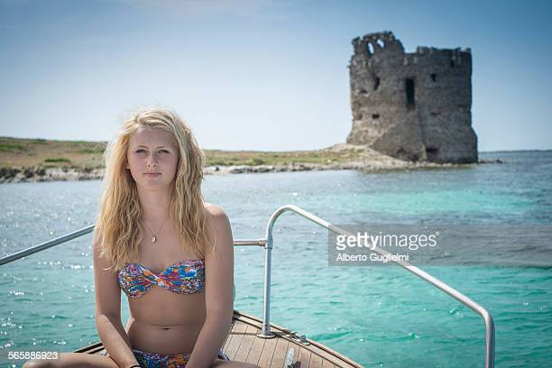 Smiling girl sunbathing on sailboat near ancient ruins