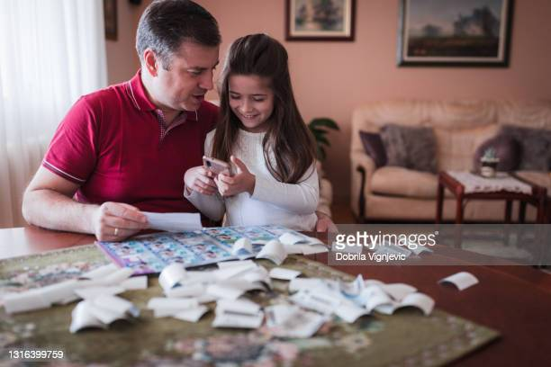 smiling girl surfing the internet via smart phone when filling in uefa sticker album with her father - final game stock pictures, royalty-free photos & images